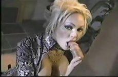Geil kijkend in de videocamera geeft zij de grote jongeheer een blowjob beurt