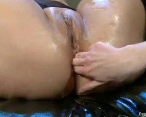 De lesbo neukt haar vriendin met een vuist in haar anus